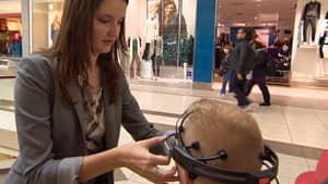 Neuromarketer Diana Lucaci adjusts eye tracking goggles on shopper Denam Drew. Lucaci uses new technologies to measure consumers' engagement, attention and memory. ()
