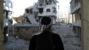 A Syrian rebel looks at houses destroyed by the Syrian Air force in a suburb of Damascus.