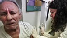 Carlos Maisonet, 73, reacts as Dr. Eva Berrios-Colon,  injects him with flu vaccine in New York. About half of confirmed flu cases in the U.S. so far are in people 65 and older.