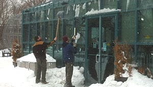 Crews knock down ice and snow from the roof at The Forks on Tuesday.