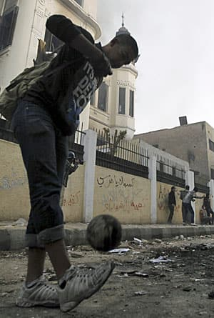 The calming effect of soccer? A young protestor plays with a ball while his fellow demonstrators throw rocks at riot police outside the interior ministry last week in Cairo.