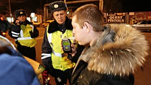 A driver uses a breathalyzer as traffic police read his blood alcohol content during a night spot check in the Siberian city of Krasnoyarsk on Oct. 17, 2012.