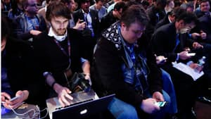 People wait for the unveiling of the PlayStation 4, a new console trying to make pre-emptive strike against Microsoft Corp's bid to make its Xbox the world's leading hub for household entertainment.