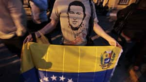 A man, wearing a shirt with an image of the late Venezuelan President Hugo Chavez, holds a Venezuelan flag during a tribute for Chavez in Tegucigalpa, Honduras on Wednesday.