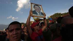 A supporter of the late Venezuelan President Hugo Chavez holds a portrait of Chavez while waiting at the street as his coffin is driven through the streets of Caracas. Authorities have not yet said where Chavez will be buried after his state funeral.