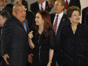 Venezuela's President Hugo Chavez, left, talks to Argentina's President Cristina Fernandez, center, as Brazil's President Dilma Rousseff looks on during the group photo of the Community of Latin American and Caribbean States, CELAC, summit in Caracas, Venezuela, Friday, Dec. 2, 2011.