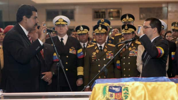 In a photo op rich in propaganda, Nicolas Maduro is symbolically sworn in as president, flanked by military leaders and standing beside Chavez's coffin. He is also holding a hand-sized copy of the country's constitution.