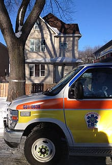 An ambulance remained at the scene Thursday morning, after a man had been convinced to come down from the roof of the house in the background.