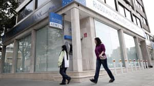 Women pass a Russian commercial bank in capital Nicosia, Cyprus on Thursday. The European Central Bank says it will keep emergency aid for Cyprus' troubled banks in place at least until Monday but will have to cut it off after that unless an international rescue program is drawn up.