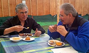 Matthew Coon Come, left, talks about his community's path to self-government over a lunch of moose and beaver meat.