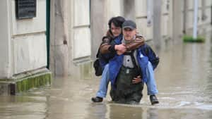 A volunteer carries a woman from her working place out of the old town of Passau, southern Germany on Monday. Flooding has spread across a large area of central Europe following heavy rainfall in recent days.