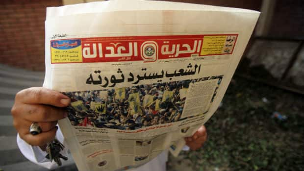 A man reads the Muslim Brotherhood's newspaper Al-Hurriya wa-l-adala. The Egyptian government has decided to dissolve the NGO, according to reports by a state-run newspaper.