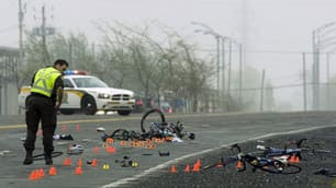 Police examine the scene where a pickup truck hit a group of cyclists, killing three and injuring three on May 14, 2010, near Rougemont, Que.