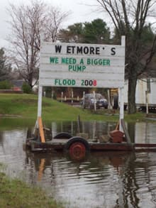 The owners of Wetmore's Nursery in St. Mary's, N.B., keep their sense of humour as the waters of the flooded St. John River take over the property.