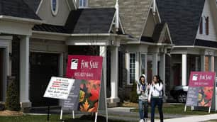 People walk past new homes that are for sale in Oakville, Ont. Low mortgage rates are helping push first-time home buyers to enter the market in droves, experts say.
