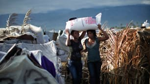 Two women carry a bag of rice in Cité Soleil, Port-au-Prince, on Feb. 18.