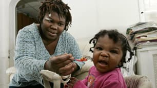 Tianna Gaines tries to feed her year-old toddler Marianna Turner, in 2009 in Philadelphia. Introducing solid foods earlier than four months of age was associated with a six-fold higher risk of obesity at age three compared with infants who had received solids later, a new study finds.