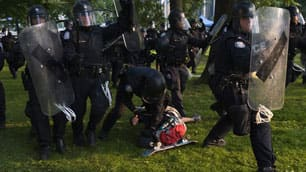 A protester is arrested by police officers at Queen's Park during a G20 demonstration in Toronto on June 26.