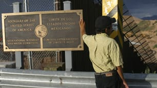 An illegal immigrant leans on a plaque marking the U.S. boundary with Mexico at Las Margaritas border crossing in Nogales, Ariz., on Monday.
