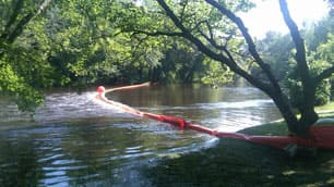 An Enbridge containment boom spans the Kalamazoo River downstream of Battle Creek, Mich.  (CBC)