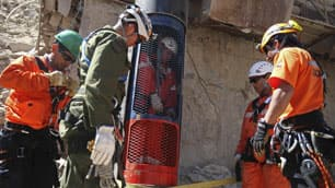 In this image released by the government of Chile, rescue workers stand next to a colleague who is inside a capsule after performing a dry-run test for the eventual rescue.