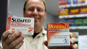 A pharmacist holds up boxes of cold medicine containing pseudoephedrine, a main ingredient used in the production of crystal methamphetamine.