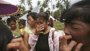 Tsunami survivors weep on the tsunami-ravaged Pagai Island, on Thursday.
