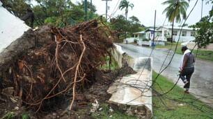 A woman walks by damaged power lines and infrastructure after tropical storm Tomas affected St. James parish, Barbados, on Saturday.