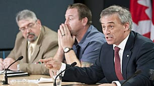 Medically discharged corporal Dennis Manuge, centre, of Musquodoboit N.S., and Ron Cundell, left, of Kettleby, Ont., listen as then veterans ombudsman and retired colonel Patrick Stogran, right, speak at a news conference in Ottawa on Aug. 17.