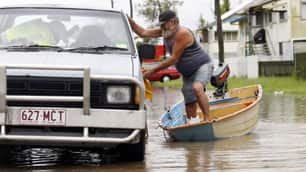 A man with an injured foot gets into his car in flooded Depot Hill in Rockhampton, Queensland, on Thursday.