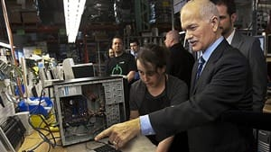 NDP Leader Jack Layton talks with a technician at a computer recycling operation during a campaign stop in Montreal on Thursday.