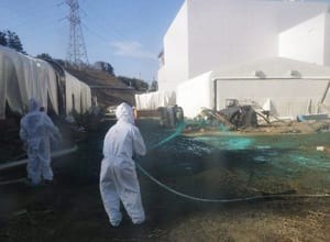 TEPCO workers experimentally spray adhesive synthetic resin over the ground at the power plant to prevent the spread of radioactive material.