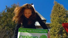 Jacqueline Romanow plants a Green Party sign outside her campaign office on Sherbrook Street in Winnipeg Monday.