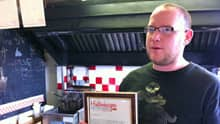 One of the owners of Hintonburger, Thomas Williams, holds a notice explaining a price increase for burgers due to the rising cost of beef.