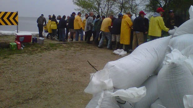 Volunteers work on sandbagging at Lake Manitoba.