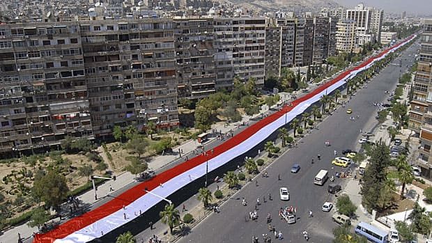 Thousands of supporters of Syrian President Bashar Assad carry a 2,300-metre-long Syrian flag in a demonstration in  Damascus on Wednesday. The Syrian government is working to stop the spectacle of Syrians fleeing in terror from government troops trying to quell the three-month rebellion.  Muzaffar Salman/Associated Press