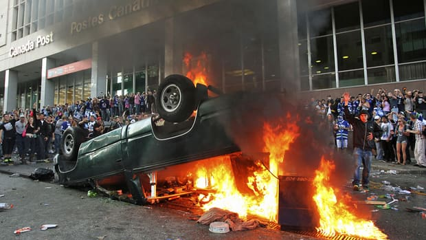 Vancouver Canucks fans watch as an overturned vehicle burns during riots in downtown Vancouver, British Columbia after the Canucks lost Game 7 of the NHL Stanley Cup playoffs to the Boston Bruins June 15, 2011.