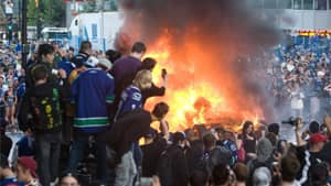 Vancouver Canucks fans watch a car burn during a riot following game 7 of the NHL Stanley Cup final in downtown Vancouver on June 15.
