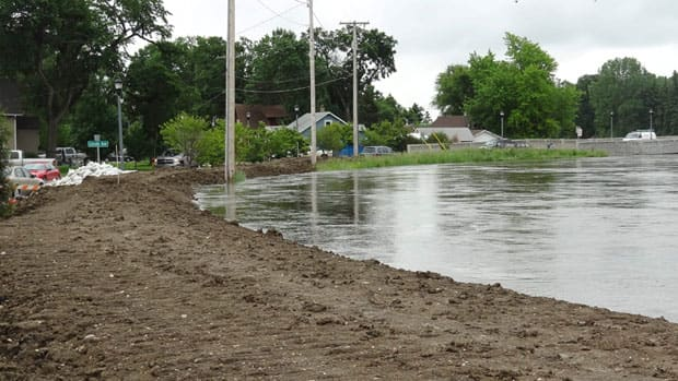 The rising Souris River passes through Minot, N.D., on Tuesday. About 11,000 residents are being ordered to leave their homes as the river gets closer to swamping the city with the worst flooding in four decades. (The Forum/Teri Finneman/Associated Press)