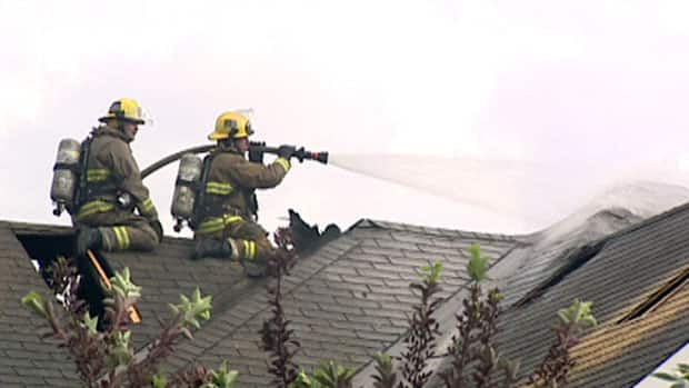 Firefighters work to contain a house fire caused by a lightning strike during Tuesday evening's storm.