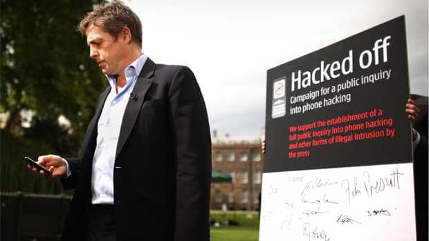 Actor Hugh Grant looks at his mobile phone as he stands in front of placard in support of the \