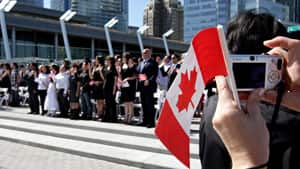 New Canadians take the oath of citizenship during a ceremony as part of Canada Day celebrations in Vancouver. Most new Canadians arrive in better health and stay healthier than the rest of the population.