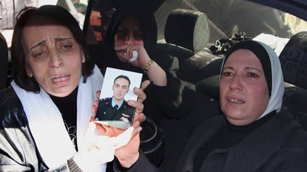 Relatives of one of the six elite pilots who the Syrian military said were killed in an ambush on Thursday mourn his death during a funeral procession on Saturday.