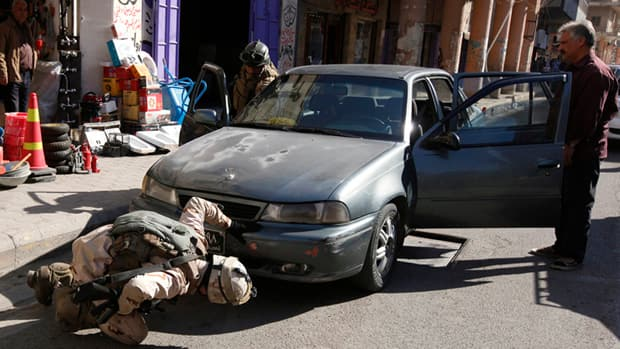 Iraqi soldiers search a car at a Baghdad checkpoint on Sunday, but they were unable to prevent a deadly suicide bombing on Monday.