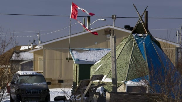 A tattered Canadian flag flies in Attawapiskat, Ont., in mid-December. Twenty-two modular homes will be transported to the remote reserve as soon as ice roads are ready.