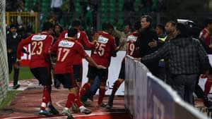 Egyptian Al-Ahly players escape from the field as fans of Al-Masry team rush to the pit.