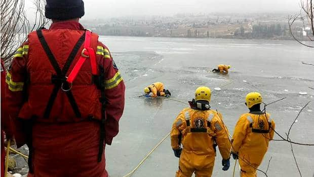 Emergency responders search for a cyclist who fell through the ice on Woods Lake north of Kelowna, B.C., on Wednesday.