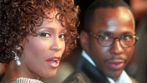 In this Oct. 13, 1997 file photo, Whitney Houston looks over her shoulder as her then husband Bobby Brown looks to her at the premiere of the movie Cinderella in Los Angeles.