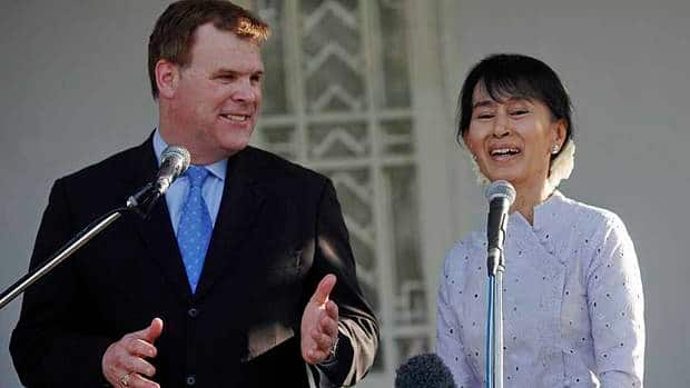 Myanmar's pro-democracy leader Aung San Suu Kyi smiles as Canada's Foreign Minister John Baird talks to reporters after their meeting at Suu Kyi's home in Rangoon Thursday.