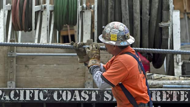 An iron worker carries steel rods at a construction site. Canada's goods-producing sector showed flat growth in May, Statistics Canada said Tuesday.
